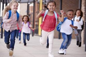 Young children running with backpacks